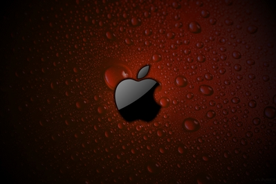 High def wallpaper of Apple logo in gloss black on red wet surface.